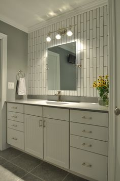Elongated white subway tile hung in a vertical pattern with dark grout.