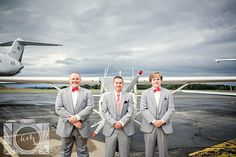 Groom and groomsmen in front of airplane picture in an airplane hangar by Amanda May Photos
