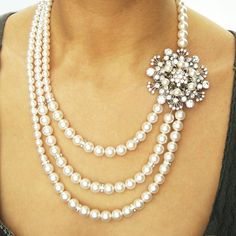 """This statement bridal necklace features a beautiful victorian style rhinestone floral pendant embellished with Swarovski pearls, offset from three strands of Swarovski pearls on one side and a single strand of pearls on the other. The flower measures 2"""". Finished with a silver plated round rhin...    $148"""