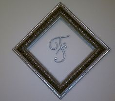 """Empty back frame found at the flea market.  """"F"""" is cake topper from wedding cake.  Hangs from the back of the picture frame via fishing line/duct tape duo."""