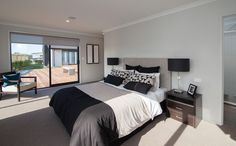 The master bedroom shows a glimpse of the huge deck that stretches across to the open plan kitchen, dining, living area. While an ensuite and walk-in-wardrobe also feature behind the bed.