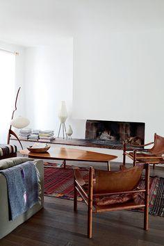 Devant une cheminée, un fauteuil en cuir et bois et une table en bois