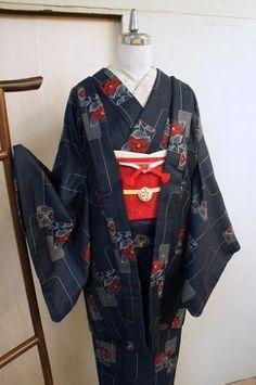 黒と紺青の糸が織りなす濃紺の地に、小窓からのぞくような椿の花枝が織り出された、夢二好みのウールのアンサンブル(着物と羽織のセット)です。