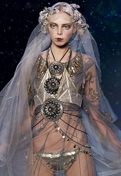 A model adorned with tinkling coins model John Galliano's Russian-style autumn-winter collection in Paris