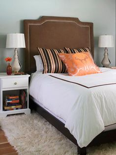 To make an extra-luxurious statement, opt for a headboard in an elegant fabric and a rich color. Here, velvet and chocolate brown are the material and color of choice. A complementary blue-and-orange color pairing balances the rich brown, while a luxurious silk throw pillow keeps up with the velvety headboard's elegant demeanor.