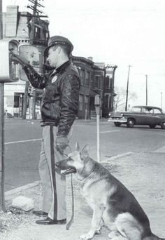 policeman with his German Shepherd at an old fashioned police call box.