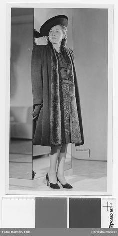 1939. Modell i mönstrad klänning och kappa med pälskrage, hatt med uppslaget brätte, pumps och handskar. Fotograf: Erik Holmén