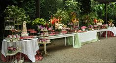 A patisserie composed of several dessert tables in a wedding at a park.