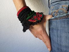 freeform crochet cuff bracelet with green and red beaded crochet flowers and black crochet lace by irregularexpressions