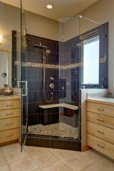 Extra large blue tiles cover the interior walls of this spacious walk in shower. Glass closes off the remaining sides for an open look. A built in bench seat is accented with a white seat top. A mosaic tile accent strip brings texture to the wall and compliments the coloring of the floor tile.