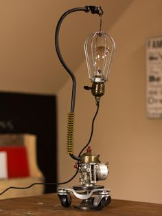 Office Desk Lamp - assembled from a car carburetor, wheels, cloth cord, & industrial cage with Edison-style light bulb.