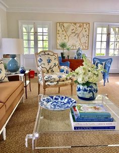 Unknown A wonderful mix in this living room with blue and white Chinese porcelain, a lucite coffee table, Chinoiserie fabrics, and shades of blue with touches of red. The neutral walls, rug, and couch