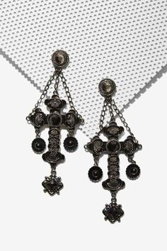 Did we just think, 'OMG' at the same time? The Jinx Earrings are gunmetal and feature cross silhouette, black and silver gems, chain detail, and post back closures.