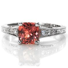Design 2351 - The 1.00 carat cushion cut Padparadscha Sapphire in this design is mesmerizing with its rare, luscious color. The tapered band has tantalizing details to compliment the center stone; the filigree and side stones near the top and the splendid hand engraving below.