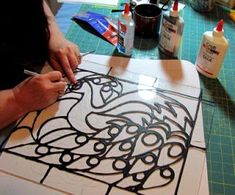 faux stained glass majestic peacock uses glue mixed with acrylics on a thrift store picture frame glass.