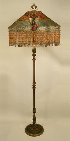 Elegant antique floor lamp holds an antique window box shade in tones of deep amber to teal green. Shade is covered in gold metallic mesh, a 1920's Spanish floral net embroidery and pristine antique French chenille flower appliqués. Colorful long hand beaded fringe with cloisonné flower beads adorn the bottom.