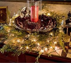 Green Scene: Nestled in a bed of greenery and Christmas lights, an early wood trencher full of chestnuts holds a red candle perched on a pile of rose hips inside a glass chimney. A pewter star and plate pick up the glow of the candle, and an early 1800s oil portrait at left counters a deep amber glass decanter at right. Written by Donna Pizzi. Photographed by Philip Clayton-Thompson. Styled by Donna Pizzi