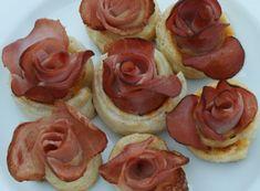 Postavte tyto šunkové růže pečené v pruzích lístkového těsta na stůl mezi chlebíčky či spousty dalších chuťovek a můžete si být stoprocentně jistí, že zmizí z talířů jako první. Ochutnat bude chtít každý a podobně budou všichni zjišťovat, jak jste ten květinový zázrak vymodelovali.