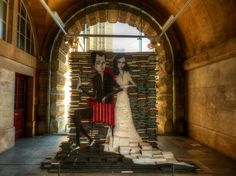Artist Mike Stilkey uses acrylic paint on backdrops made out of books, including this piece on display at the Bristol Museum -- from Mental Floss