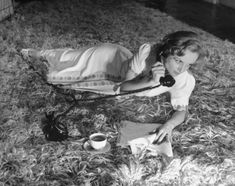 Carole Lombard drinks a cup of coffee and talks on the telephone while lounging on the floor of her Hollywood home in October 1939,