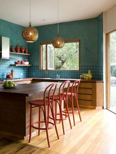 turquoise walls, gold globe pendants, red accents and bar stools - love this kitchen!