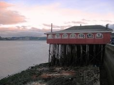 """Chiloe, in Castro's port a typical chilote """"palafito"""" structure (basically, a house–or, in this case, restaurant–on stilts). Many of Chiloe's palafitos have been destroyed by earthquakes, but some remain here and there."""