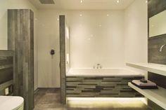 (De Eerste Kamer) In deze badkamer is de onderplint van het bad indirect verlicht. Op de achterand van het bad zijn een tweetal verlichte nisjes geplaatst. De warme grijze wand- en vloertegels zijn gecombineerd met grote hoogglans witte tegels. In de inloopdouche is een luxe plafonddouche opgesteld met Led-verlichting. De strakke wastafel in wit composiet met bijpassende kraan maakt de badkamer helemaal af. Meer foto's kunt u vinden op www.eerstekamerbadkamers.nl