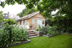 Backyard summerhouse urban outbuilding London ; GardenistaSets of double doors on two walls swing open to help obliterate the boundary between outdoors and in.