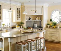 Kitchen Cabinets - Creamy Tones Soften the look of a kitchen by choosing off-white (rather than bright white) cabinets. This ivory hue works well with the brown wood tones and blue tiled backsplash for a room with elegant style.