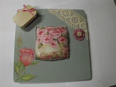 Pin cushion in a wooden frame.  Little tin button box held on by a magnet that is glued onto the frame.
