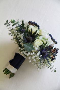 Bridal Bouquet with winter white Avalanche Roses, Blue Eryngium Thistles, Classic Hydrangeas, Midnight Blue Viburnum Berries, Eucalyptus Globus and white Freesia and Gypsophilia, Diamante detail and a very snazzy semi naked handle completes the design