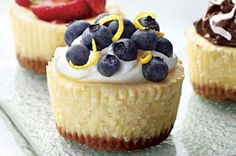 PHILADELPHIA Mini Cheesecakes 1 cup graham cracker crumbs 3/4 cup plus 2 Tbsp. sugar, divided 6 Tbsp. butter or margarine, melted 3 pkg. (8 oz. each) PHILADELPHIA Cream Cheese, softened 1 tsp. vanilla 3 eggs 1 cup whipping cream 2 cups blueberries 1 Tbsp. lemon zest