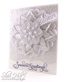 "I started with a mix of white cardstock and a pearl cardstock from WorldWin Papers. My white card base is 4-1/4"" x 5-1/2"". I cut the pearl cardstock 1/4"" smaller and embossed with Spellbinders Ocean Dreams M-Bossabilities folder.I decided to stamp the sentiment on the bottom so I cut a decorative edge with Spellbinders A2 Bracket Borders One die and picked a sentiment from JustRite Large Fancy Holiday Sentiments clear stamps to stamp directly on my card base."