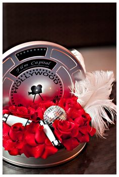 Film cans fileld with floral and ostrich feathers can personalize the film cans, or use actual vintage film cans.