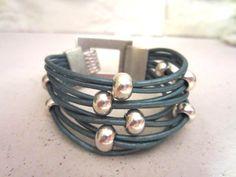 pulsera realizada con cuero turquesa , cierre de gancho y bolas con baño de plata