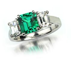 Classic and Timeless Emerald and Diamond Ring Flawless and brilliant, Fine Gem Quality 1.33ct emerald with two emerald cut 1.30 EF-VS diamonds total weight