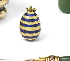 An enamelled gold miniature pendant egg, maker's mark BC, circa 1900 the ovoid body striped in the alternating blue and yellow Rothschild colours.