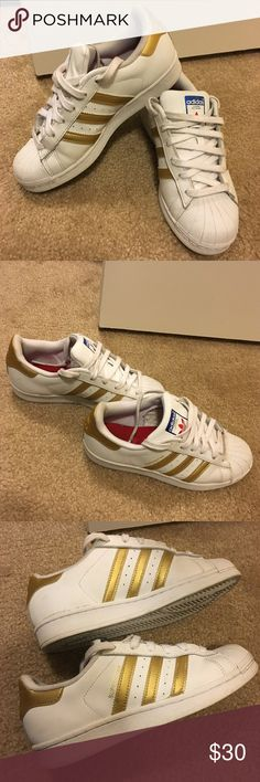 Adidas Superstar Sneakers White leather with gold stripes. Good condition. NOTE: Shoes are a Women's size 5.5 which fit a Women sz 7  due to the shoe running big. adidas Shoes Athletic Shoes
