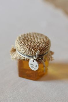 Newlyweds are gifting local jars of honey with sweet details such as bee charms, wooden honey dippers, and colorful ribbon.
