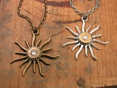"""This necklace is """"HOT""""!!! Features an interesting sunburst or sun pendant showcasing a brass bullet casing for it's core. Fire power surrounded by the fiery heat of the sun. We call this our """"Hot Caliber"""" necklace! Necklace is offered using antique silver or antique brass components. Hangs from a sturdy coordinating cable chain. Swarovski crystals are optional. Use the dropdown to make all of your selections. Diameter of pendant: 2 inchesLength: standard 18""""Lobster Closure NOTE: We use…"""