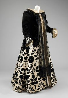 This evening coat readily includes iconography of the Tudors with a Tudor rose pattern alongside the silhouette of alternative 16th century negligées in the full sleeves, standing collar and unfitted style.
