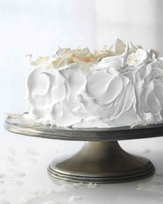 Raspberry White Cake | Martha Stewart Living - This cake is made with cream for a luxuriously rich texture. Cut through the fluffy meringue frosting to reveal the raspberry-flecked cake layers with raspberry jam in between.