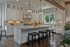 Hardwood floors, white cabinetry, great lighting, backsplash, and a touch of the large ceiling beams. All-in-one.