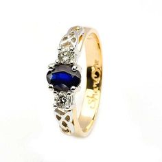 This Shanore Diamond and Sapphire 3 stone engagement ring displays the trinity knot, a classic Celtic symbol of everlasting love. Made with exquisite 14 karat yellow and white gold, the ring is crowned by 2 brilliant cut diamonds on either side of a beautiful oval sapphire. The color scheme of gold, white gold and sapphire gives this elegant ring a defined style. Historic MeaningCeltic jewelers and artists have clung tightly to a number of classic symbols of love throughout history. Seen…