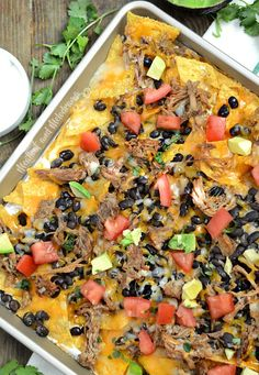Sheet Pan Pulled Pork Nachos are loaded with meat, cheese, black beans and your favorite toppings and cooked on a sheet pan for easy clean-up. It's a quick and easy dinner or appetizer made with leftover pork roast and ready in about 20 minutes!