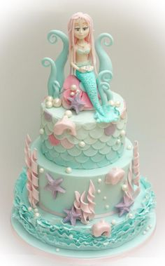 Pretty mermaid and dolphin themed birthday cake. I used the Maggie Austin ruffle technique on the bottom tier, which was three cake boards sandwiched together and covered. I liked how the ruffles gave it a more romantic, girlie feel. The middle...