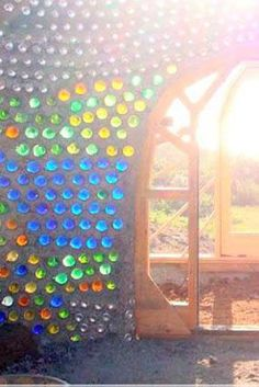 Gorgeous earthship with colored glass bottles. Bottle House, Bottle Garden, Glass Garden, Glass House, Earthship Home, Earth Homes, Natural Building, Green Building, Glass Bottles