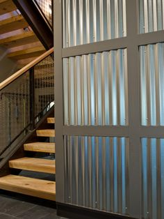 The foyer's far wall is framed out with painted pine trim. Inside each 34-inch square lies a panel of corrugated steel, a rustic building material that finds a new sleek, sophisticated interior application.