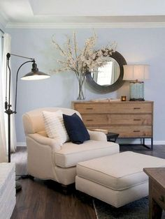 As seen on HGTV's Fixer Upper, a comfy armchair is adorned with a navy throw pillows and sits in the newly renovated living room of the Gaspar home. A dresser becomes a storage space topped with a lamp and decorative flowers. A round mirror is placed abov Living Room Flooring, Home Living Room, Living Room Decor, Living Spaces, Bedroom Decor, Bedroom Chair, Bedroom Lighting, Bedroom Ideas, Bedroom Furniture