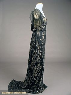 WORTH EVENING GOWN, PARIS, c. 1908. Black silk satin brocade w/ silver lame frond pattern, Empire trained gown w/ 3 rows grey-blue diamante trim on black silk tulle sleeves.